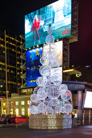Traditional Christmas tree at Yonge-Dundas Square during the nighttime. The intersection attracts millions of tourists every year. Billboard advertising in the background.