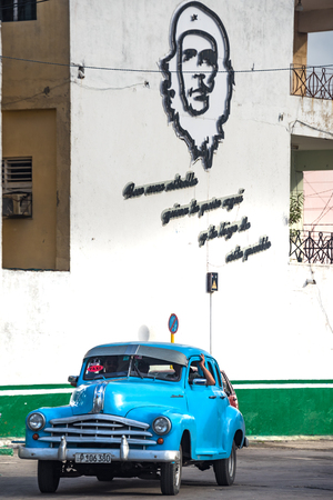 Che Guevara urban sculpture on the wall of a centric gas station. An old American car is parked below it