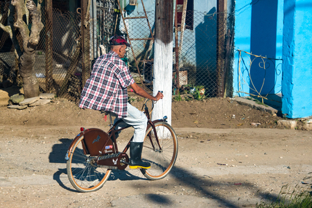Cuban man riding a bicycle in the rural area. An old man in cap and boots riding a bike on a dirt road. After the special period bicycles became an integral part of the Cuban people lifestyle.