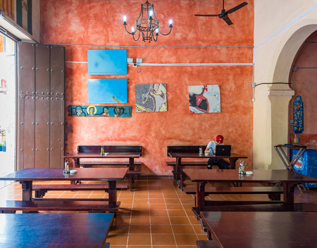 Indoors at the Don Cayetano Bodegon. Sitting area of a small eatery with rows of tables and benches Don Cayetano Bodegon