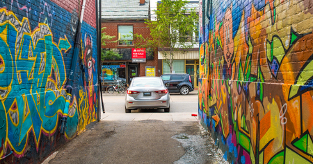 Car leaving an alleyway full of colorful urban graffiti. Urban scene in the Capital city of the province of Ontario