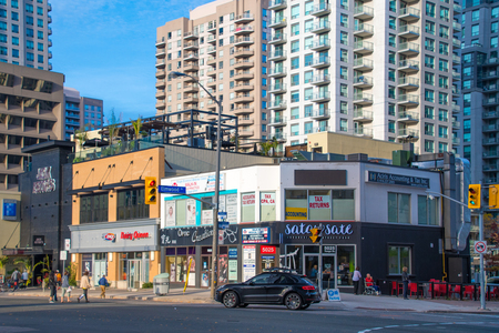 Yonge Street lifestyles and contrasts. Small family business contrasted against large apartment buildings. The boom in real estate is threatening the disappearance of the vintage small properties. Editorial