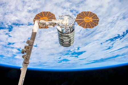 Cygnus cargo ship is captured by the Canadarm in space. Image courtesy of . Фото со стока