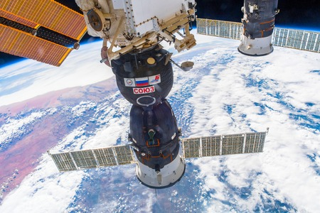 Outer Space-December 30, 2017: Awesome view of the planet Earth and the Soyuz spaceship docked to the ISS.
