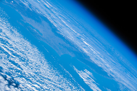 Close up of planet Earth edge. Contrast of the awesome blue and white against the dark background of space.