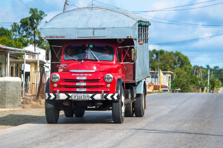 Red Chevrolet truck for passenger transportation. Old obsolete Cuban truck driving on the road during the daytime. Images of Cuba