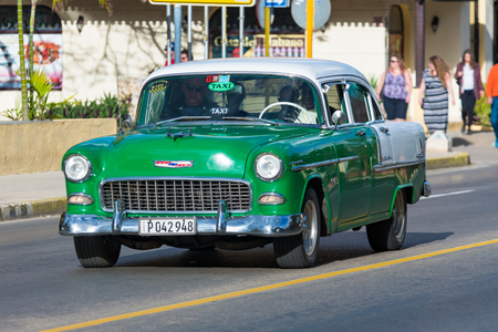 Old vintage cars in action. The green and white Chevrolet drives in the First Avenue of the resort town. This kind of obsolete vehicles have become a tourist attraction in the Caribbean Island Editorial