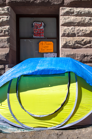 Canadian First Nations occupy the Old City Hall in protest to diverse social issues they are facing. Tent in the front wall of the landmark building. There are signs stuck in the window of the famous building
