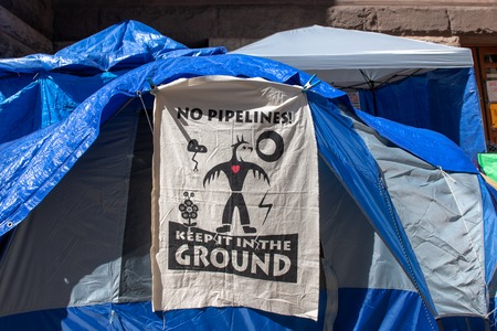 Canadian First Nations occupy the Old City Hall in protest to diverse social issues they are facing. Protesting the pipelines, a textile banner at the entrance of a tent.