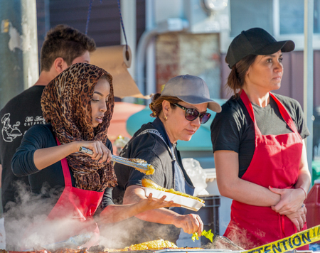 Muslim woman wearing hijab serves food in street food stand during Dundas West Festival in Little Portugal neighborhood, the festival is a tradition enjoyed by the multicultural city every year.