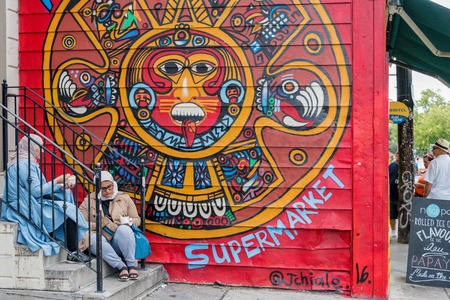 Muslim women sitting at Mayan cultural symbol painted on wall at Kensington market. Toronto multiculturalism