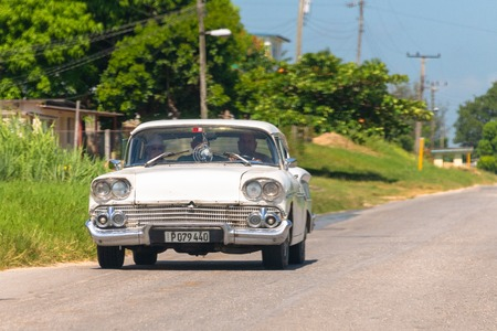 Old white vintage car driving on a rural road during the daytime. The typical blue and green colors of the tropical climate can be seen in the background.