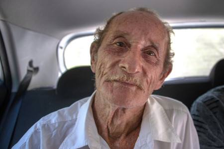 Cuban senior man hitchhiking with tourists in the area of Jibacoa. His reddish hair  and white skin indicates that his family members were immigrants to the island in the past.