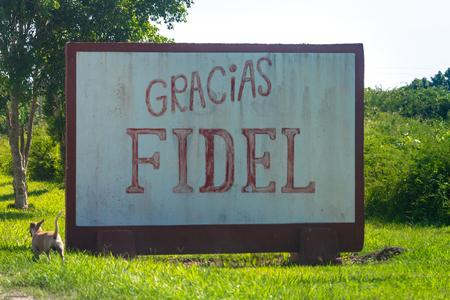 A cement sing reads: Thanks Fidel (Spanish: Gracias Fidel). The sign is located by a country road. There is a stray dog on the side. After his passing, many symbols referring to Fidel Castro has appeared throughout the Caribbean island