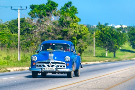 Vintage Cuban  blue car driving in the Varadero highway.  The vehicle is working as a taxi. The Caribbean island is known for the high number of obsolete vehicles driving on its roads. Editorial