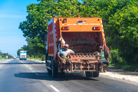 Two male garbage collectors sitting in the back of the truck without any protection. The truck is driving in the Varadero highway during the day