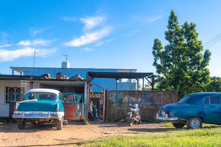A private car body shop on a rural area. There are two vintage obsolete cars waiting outside. Editorial
