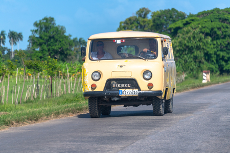 Obsolete microbus known in the Caribbean island as guasabita or wasabita.  The land vehicle drives on a country road during the day.