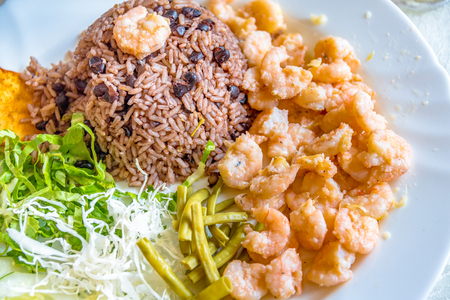 Cuban cuisine in plate containing rice, prawns and salads. The meal is served at a privately owned restaurant at an inexpensive price.