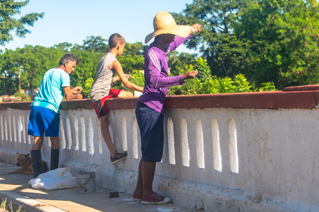 A man and two children fishing on a bridge over a rural road during the day. This kind of fishing practice is more aimed at recreation