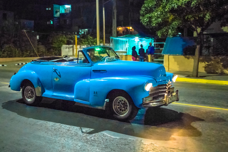 Old vintage American blue car in action at night. The traditional colorful vehicles have the headlights on. They are a tourist attraction in the Caribbean Island.