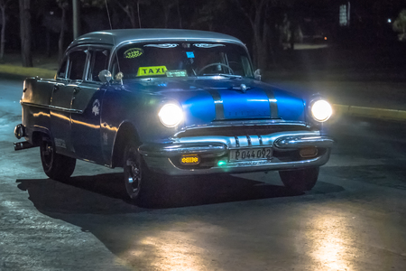 Old vintage American blue taxi car in action at night. The traditional colorful vehicles have the headlights on. They are a tourist attraction in the Caribbean Island. Editorial