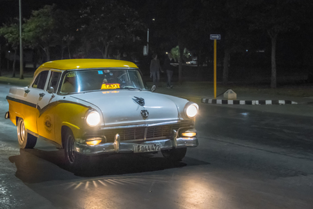 Old vintage American taxi yellow and white car in action at night. The traditional colorful vehicles have the headlights on. They are a tourist attraction in the Caribbean Island. Editorial