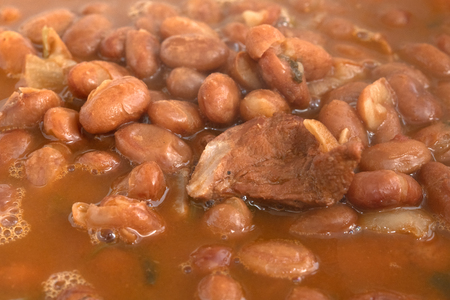 Close up of a hot red kidney beans soup. There is a small piece of pork meat in the food