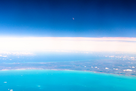 The coast of South Carolina seen from a commercial plane. The moon is seen in a blue sky and over a line of white clouds