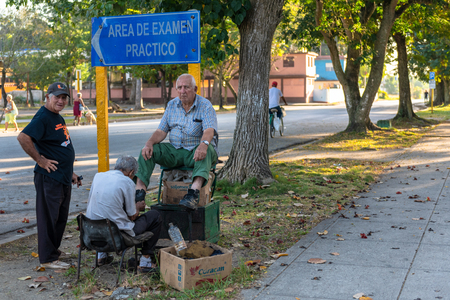Senior men in a shining shoe seat. One of them works self employed to compliment his retirement cheque. The other one, gets his shoes cleaned.  A third man stands close to the other two. Reklamní fotografie - 115967441