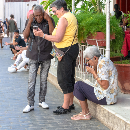 Senior Cuban people using the internet (wifi) in the city promenade or boulevard during the day