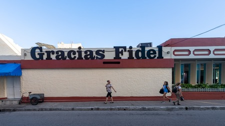 Santa Clara, Villa Clara, Cuba-November 4, 2018:  A sign of Gracias Fidel in the Marta Abreu street. Real life people walking in the sidewalk