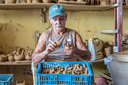 Employees working in ceramic items in the Potter House or Casa del Alfarero run by Daniel Chichi Santander. The potter shop or taller del alfarero works on most of the reconstruction and revitalization projects for vintage buildings in the island. Редакционное