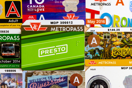Presto Card over a background of old Metropasses. The Toronto Transit Commision is transitioning from the ole metropass system to the modern Presto Cards.