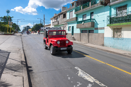 Red Willys jeep driving in the Central Road during the day