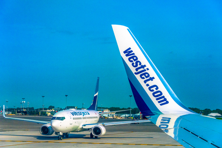 Westjet Boeing commercial passenger planes  lining up to take off at the Pierre Elliott Trudeau airport in Montreal city in daytime.