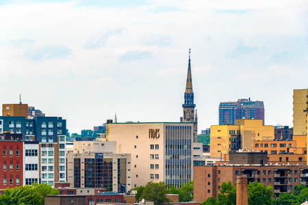 City skyline with architectural contrast. Cloudy sky above buildings with a old church in the middle. Editorial