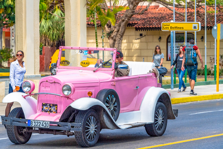 Cuban cars: Close up of a pink and white vintage taxi running outside a hotel.