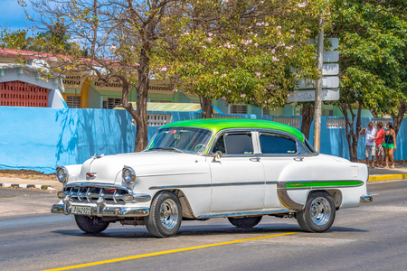 Cuban vehicles: White car with green roof passing by on a not so crowded small city road. Editorial