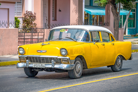 Cuban old cars: Small yellow taxi with white roof passing by in front of small houses. 에디토리얼