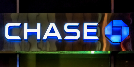 Financial institutions in New York: Chase bank signage and logo glowing on its building in NYC.  JPMorgan Chase Bank, N.A., doing business as Chase, is a national bank that constitutes the consumer and commercial banking subsidiary of the multinational ba Publikacyjne