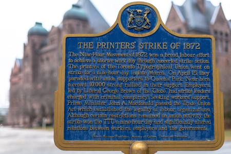 Historic plaque of the Printers Strike of 1872. The Queens Park building can be seen in the background. Toronto history and famous places.