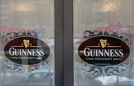 Tempered glass with the sign of Guinness beer.  The beautiful doors are the entrance to a bar in Church Street area Редакционное