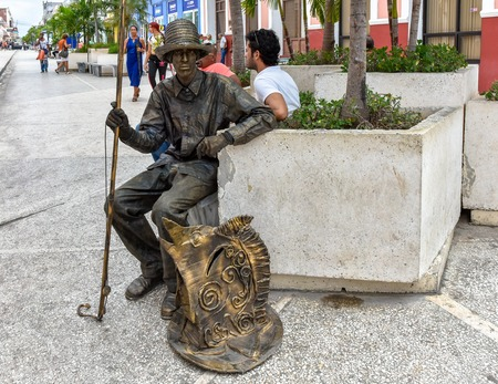 Living statue of a fisherman. The artist sits in the city boulevard or promenade. The area is a tourist attraction. The person works for tips or donations from tourists.