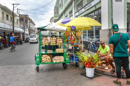 Private seller cart in the city center. It is full of homemade crackers. By its side there is a bucket of flowers for sale. The owners happily talk with a tourist. Cuban people lifestyle Editorial
