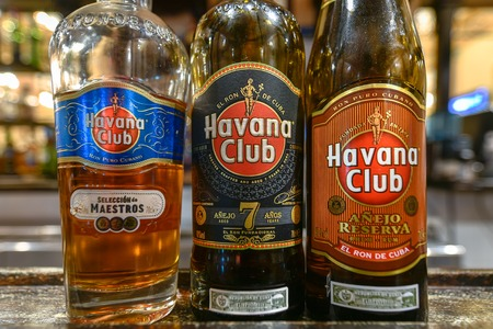 Three bottles of Havana Club rum in the counter of a bar.  The variety decrease quality and price from right to left. The bottles are a 'masters selection', 7 years old, and 'reserve'
