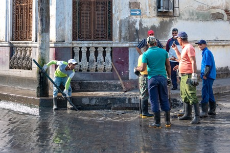 Communal workers cleaning a catch basin on a city street. Cuban people lifestyle. A catch basin is also known as storm drain or storm sewer