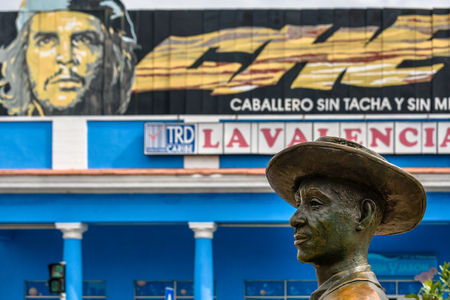 Benny More bronze statue in 'El Prado'.  The art object contrasts with an image of Che Guevara in the background. The place is a tourist attraction and famous place in the Southern city of the Caribbean island Stock Photo - 117657201
