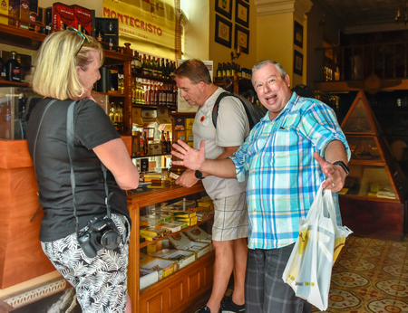 Tourists buying cigars in Casa del Habano. One of the tourists have fun with the photographer by humorously posing for the image Editorial