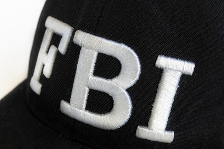 Close up of the FBI logo on a black cap. The text stands for Federal Bureau of Investigations